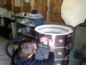Tanner Harris working on an electric kiln